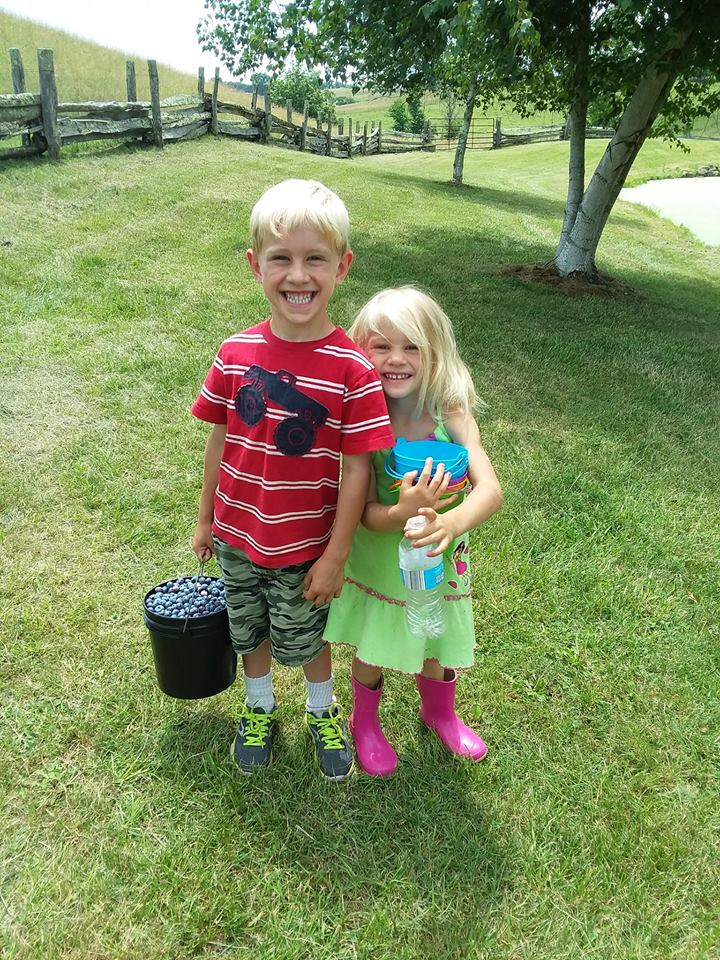 Kids with local fruit (blueberries).